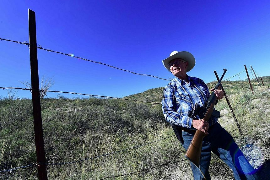 Cattle rancher Jim Chilton stands beside a fence that is the US-Mexico border on part of his 50,000 acre ranch.