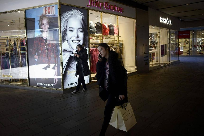 A woman uses her mobile phone as she walks past a store in Beijing on Jan 13, 2017.