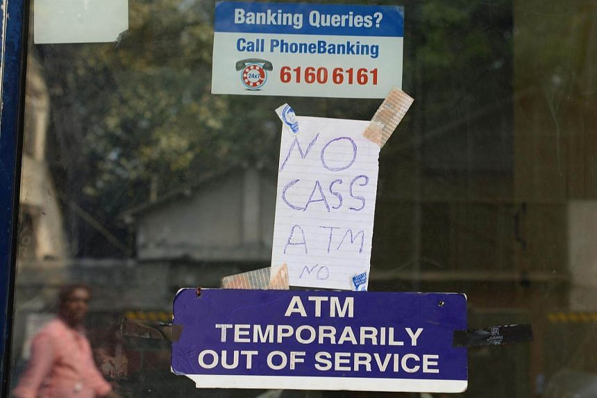 A handwritten sign stating 'no cash' is hung onto door of an ATM in Mumbai.