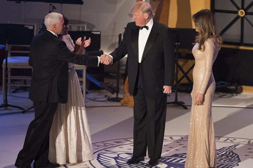 US Vice President-elect Mike Pence, with his wife Karen Pence, shakes hands with US President-elect Donald Trump next to incoming First Lady Melania Trump during the candlelight dinner at Union Station in Washington, DC, US, on Jan 19, 2017.