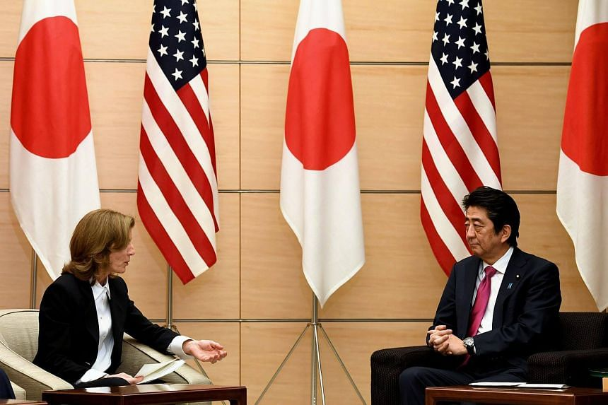 Japan's Prime Minister Shinzo Abe (right) listening to US Ambassador to Japan Caroline Kennedy during a joint announcement of the return of US military land on the island of Okinawa.
