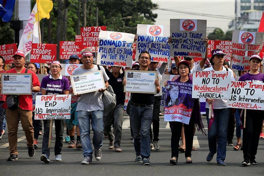 Protesters display anti US President-elect Donald Trump placards while marching outside the US embassy in metro Manila, Philippines on Jan 20, 2017.
