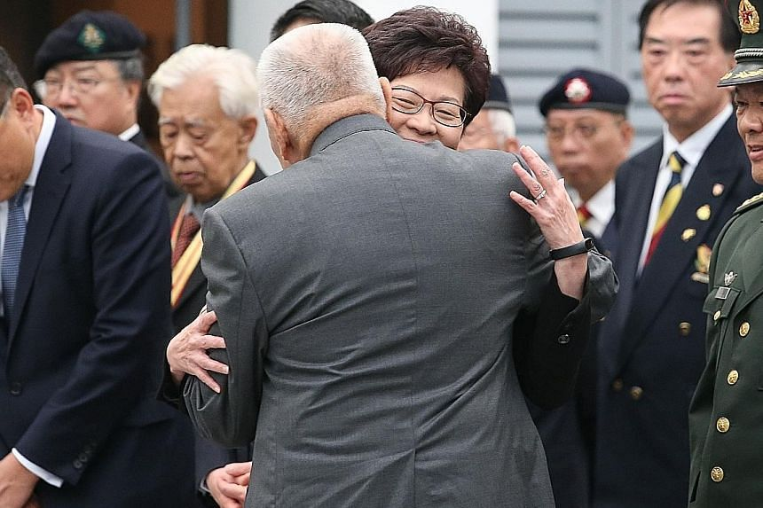 Former chief executive Mr Tung hugging Mrs Lam last month. Mrs Lam says Mr Tung has stopped his usual practice of hugging her to avoid speculation that she has been favoured for the chief executive job.