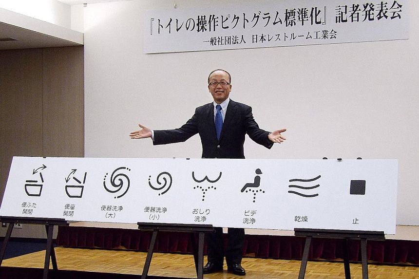 Mr Madoka Kitamura, chairman of the Japan Sanitary Equipment Industry Association, showing off the standardised icons for high-tech toilet functions in Tokyo.