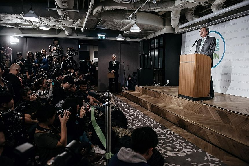 Mr Tsang (at the podium) announcing his bid for the city's top job at a news conference yesterday in Hong Kong. He was spotted holding a mobile phone with the mascot of the crisp brand Mr Pringles on it. The former Hong Kong finance chief, who has be