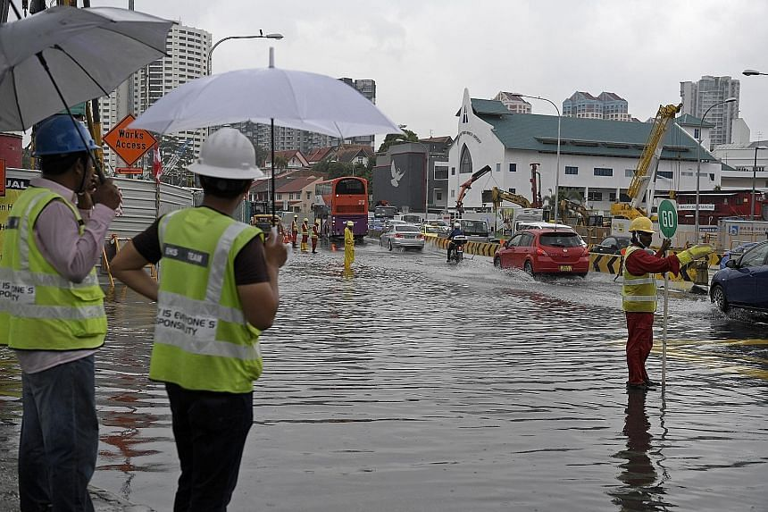 Workers from a nearby construction site directing traffic away from rising flood waters. Upper Thomson Road was hit by a second flash flood in as many months yesterday, with photos on social media showing vehicles with up to half their tyres in water