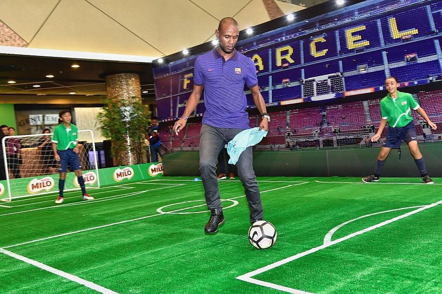 Four-time La Liga champion Eric Abidal playing football with children from FCBEscola Singapore - the Barcelona football school here - at a Milo event at the Sports Hub yesterday.