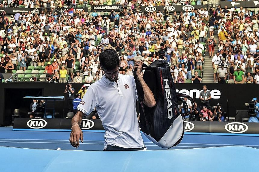 Defending champion Novak Djokovic leaving the court after his 7-6 (10-8), 5-7, 2-6, 7-6 (7-5), 6-4 loss to Denis Istomin of Uzbekistan in the second round of the Australian Open yesterday.