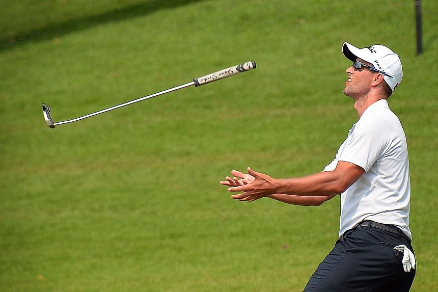 Former world No. 1 Adam Scott throws his putter in frustration at the par-four ninth hole at Sentosa's Serapong course. The Australian made par at that hole but dropped shots at the par-five seventh (triple bogey) and par-three eighth (bogey). The th