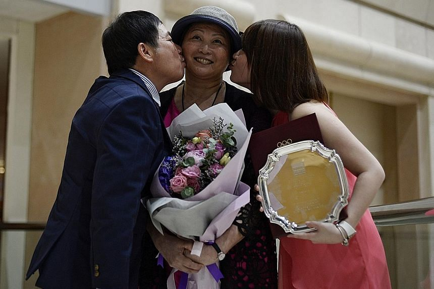 Gymnastics coach Zhu Xiaoping receiving kisses from her husband Lin Zhenqiu and daughter Pan Pan after getting a special award for fortitude at the Singapore Sports Awards last year.