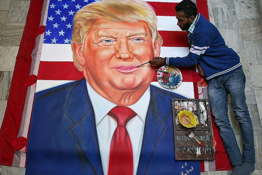 In Amritsar, India, artist Jagjot Singh Rubal readies his portrait of Mr Trump in honour of the US President-elect's inauguration. Mr Rubal has painted portraits of several politicians, including that of British Prime Minister Theresa May.