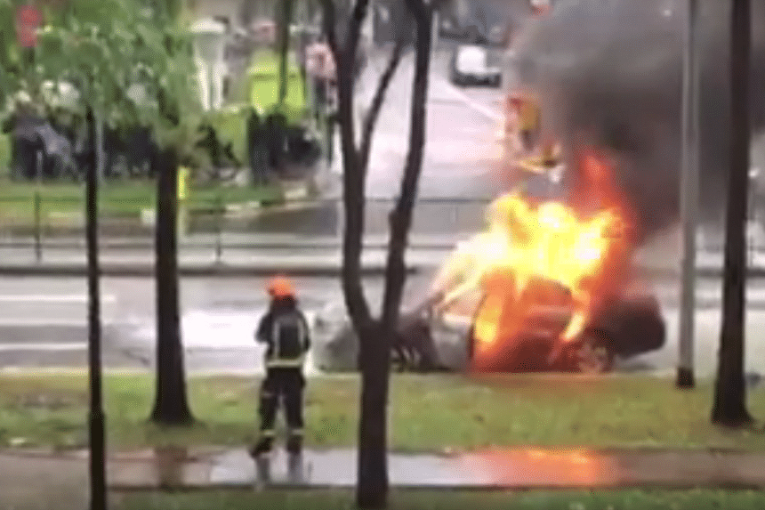Bystanders watch as a fire rages in a cab at Woodlands Avenue 6 on Thursday evening.