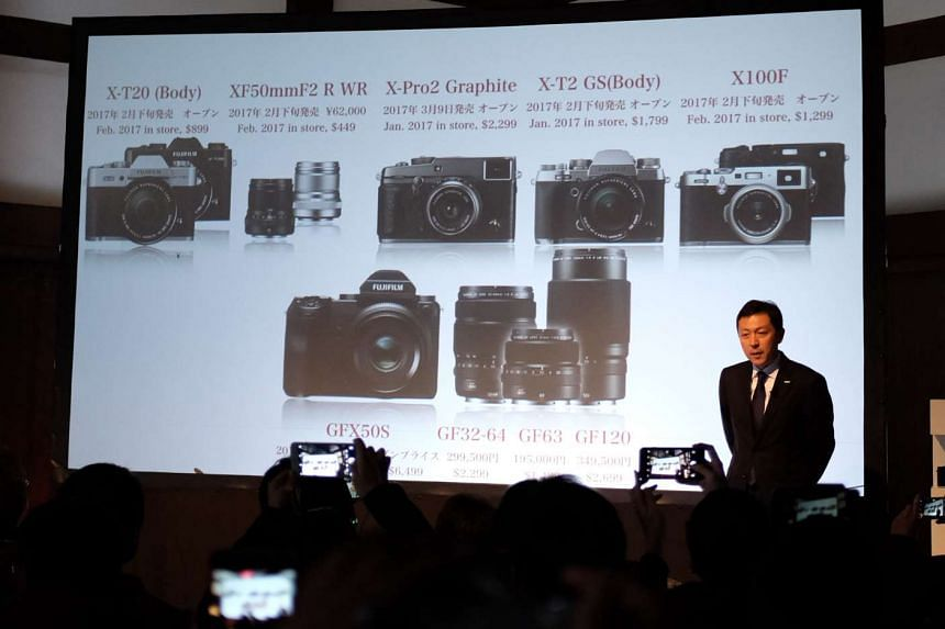 Fujifilm sales and marketing general manager Toshihisa Iida showing off the imaging giant's product line up during the press conference in Kyoto.