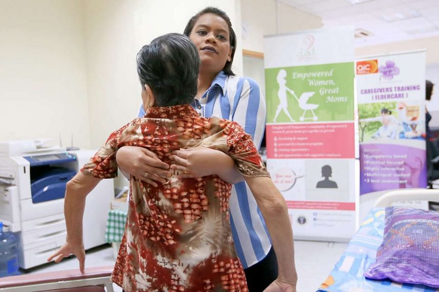 Madam Nur Fadzelah Sapullah, a volunteer at Daughters of Tomorrow (DOT), demonstrates how to carry an elderly patient.