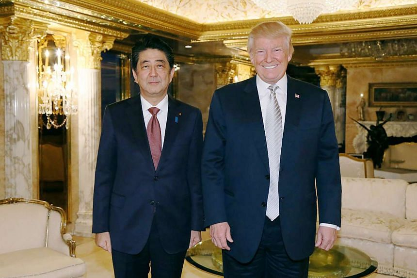 Japanese Prime Minister Shinzo Abe (left) and US President-elect Donald Trump (right) pose for a photograher in New York in November 2016.