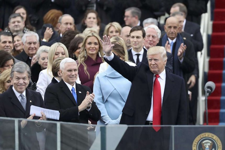 Donald Trump waves as he arrives to be inaugurated during ceremonies on the Capitol in Washington, Jan 20, 2017.