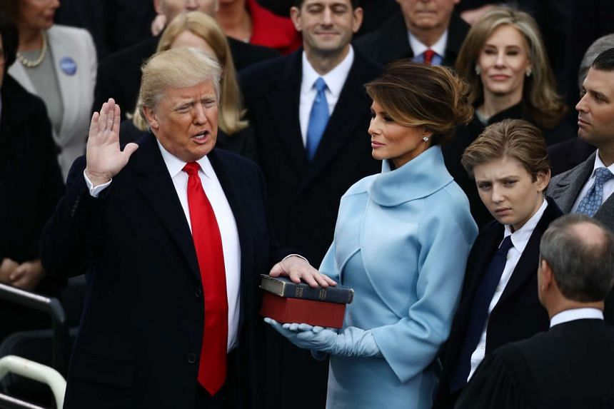 US President-elect Donald Trump takes the oath of office as First Lady-elect Melania Trump stands during the 58th presidential inauguration in Washington, D.C., US on Friday, Jan 20, 2017.