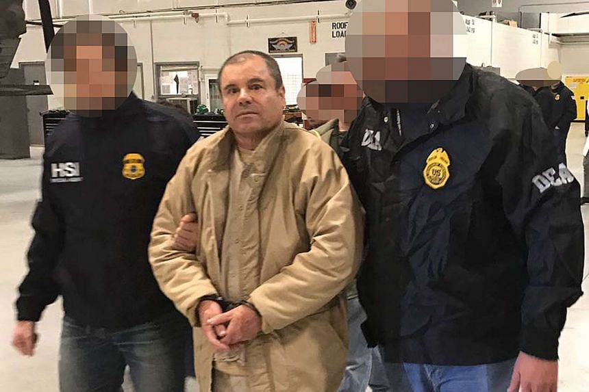 """This handout picture released by the Mexican Interior Ministry on Jan 19, 2017 shows Joaquin Guzman Loera aka """"El Chapo"""" Guzman (centre) escorted in Ciudad Juarez by the Mexican police as he is extradited to the United States."""