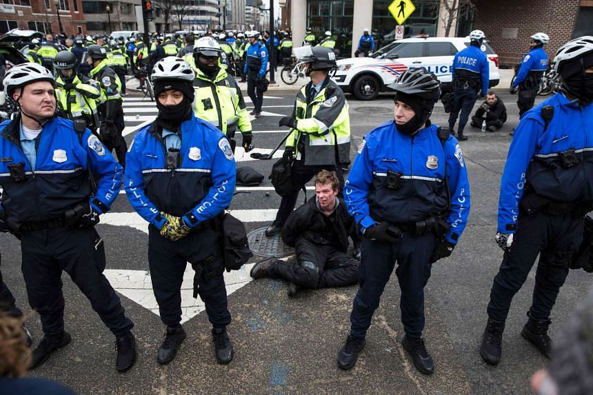 Police officers detain a protester before the inauguration of President-elect Donald Trump Jan 20, 2017, in Washington.