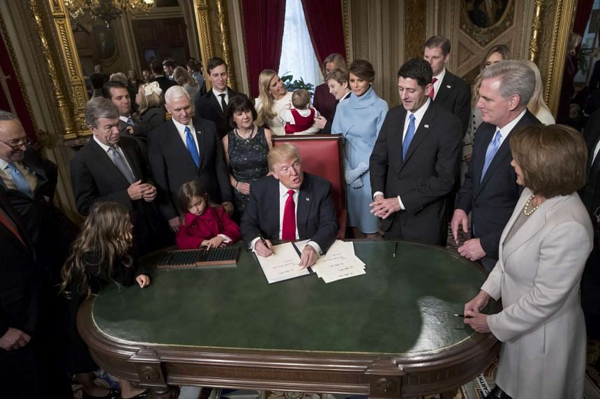 President Donald Trump is joined by the Congressional leadership and his family as he formally signs his Cabinet nominations into law, Jan 20, 2017.