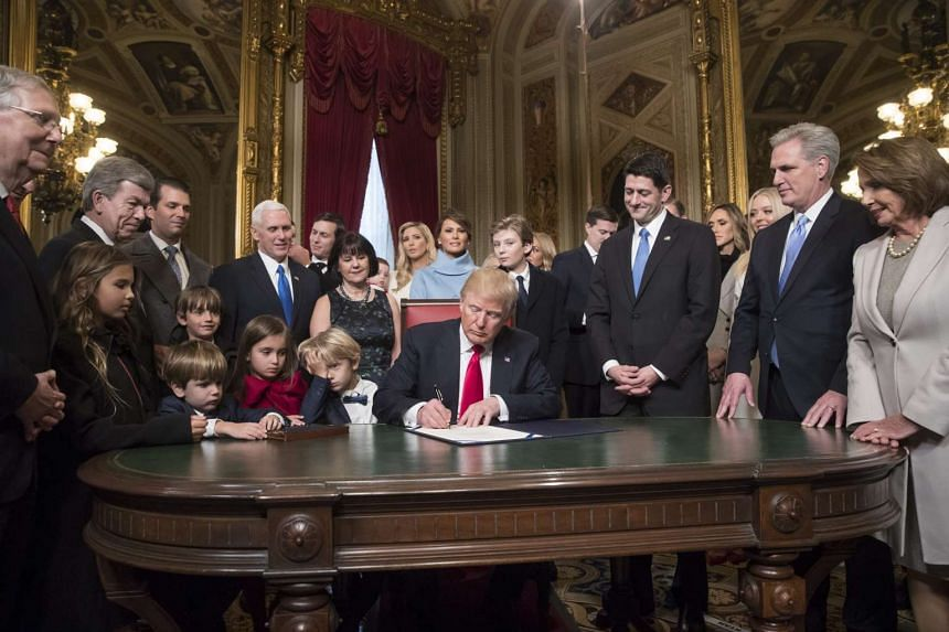 US President Donald Trump (centre) is joined by the Congressional leadership and his family as he formally signs his cabinet nominations into law, in the President's Room of the Senate, at the Capitol in Washington, DC, USA, on Jan 20, 2017.