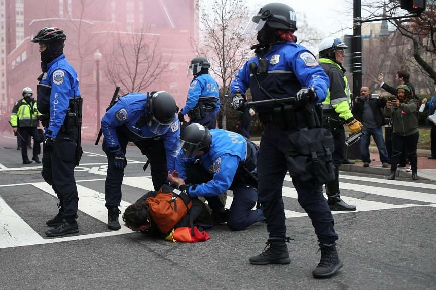 Police detain an activist during a protest against US President Donald Trump.