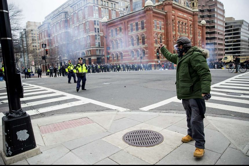 A demonstrator gestures to police officers during a protest at the 58th presidential inauguration.