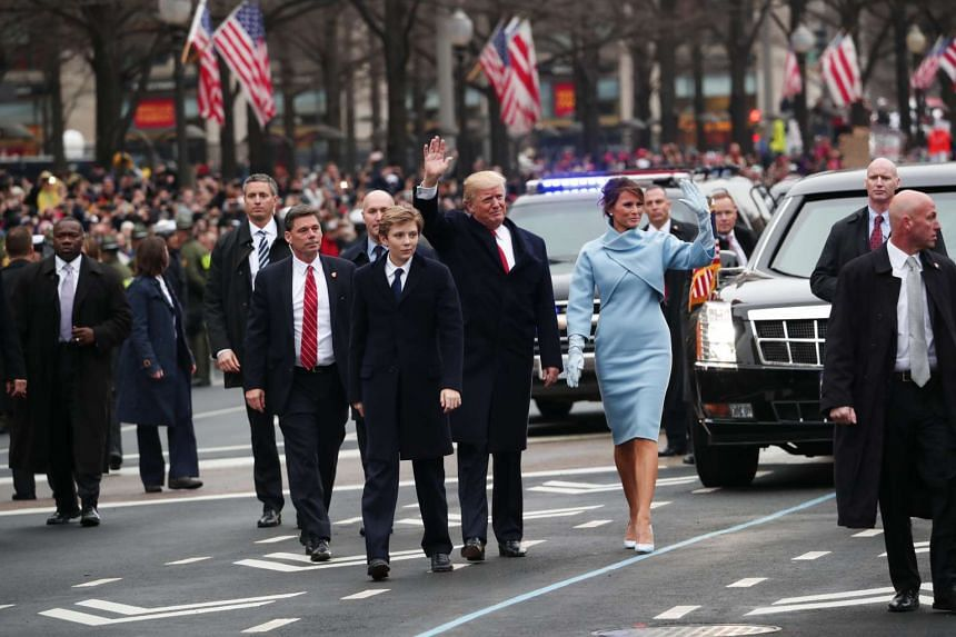 President Donald Trump and first lady Melania Trump walk briefly with their son Barron on the inauguration parade route in Washington, Jan 20, 2017.