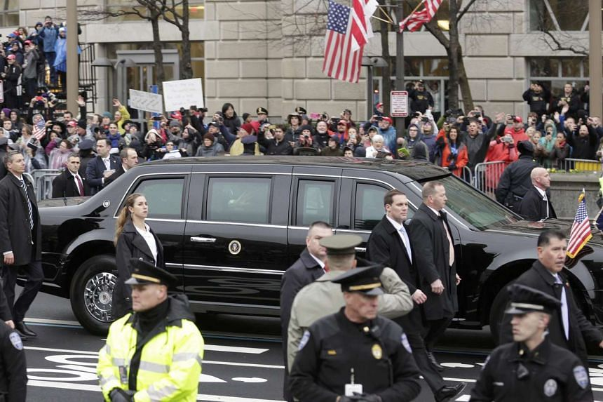 Secret Service agents walk alongside US President Donald Trump's limousine as he participates in the inaugural parade after his swearing in, Jan 20, 2017.