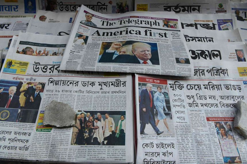 Indian newspapers carrying front-page news of the inauguration of US President Donald Trump, at a newspaper stand in Siliguri, on Jan 21, 2017.