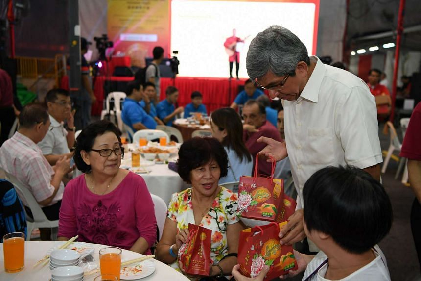 Associate Professor Yaacob Ibrahim handing out oranges and delivering his festive wishes to needy residents from Jalan Besar GRC and Potong Pasir SMC at Harmony Night.