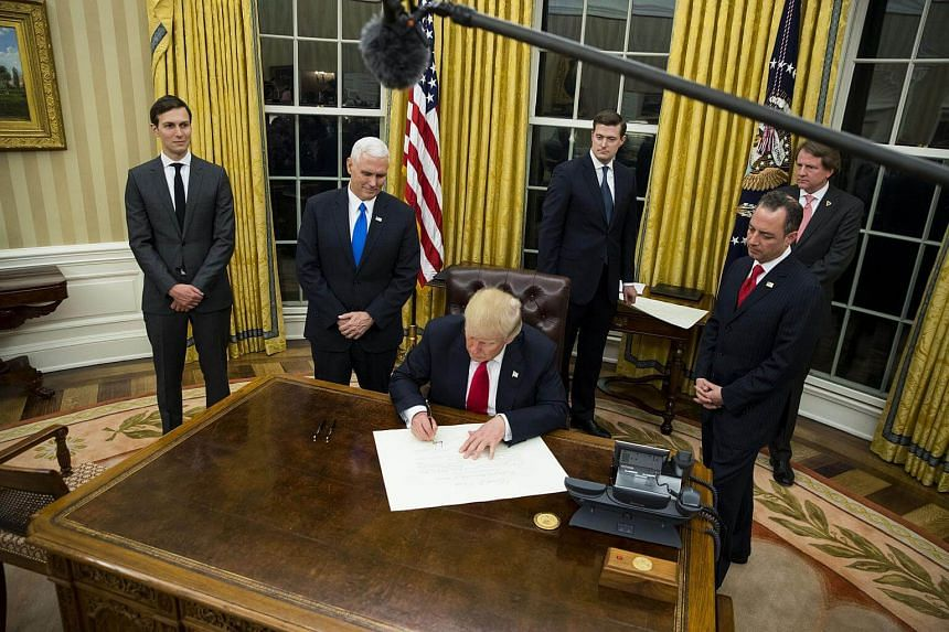 US President Donald Trump signing an executive order on his first evening in the Oval Office, at the White House in Washington, on Jan 20, 2017.