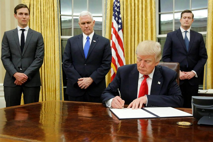 US President Donald Trump, flanked by (from left) Senior Advisor Jared Kushner, Vice President Mike Pence and Staff Secretary Rob Porter, welcomes reporters into the Oval Office for him to sign his first executive orders at the White House in Washing