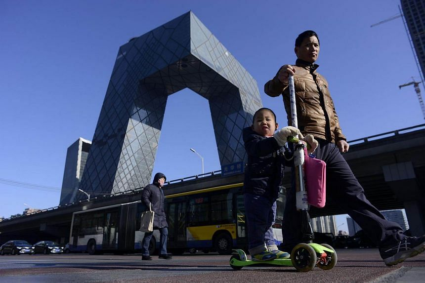 A man crosses a street with a child as the CCTV Tower looms in the background in the central business district in Beijing, China on Jan 20, 2017.