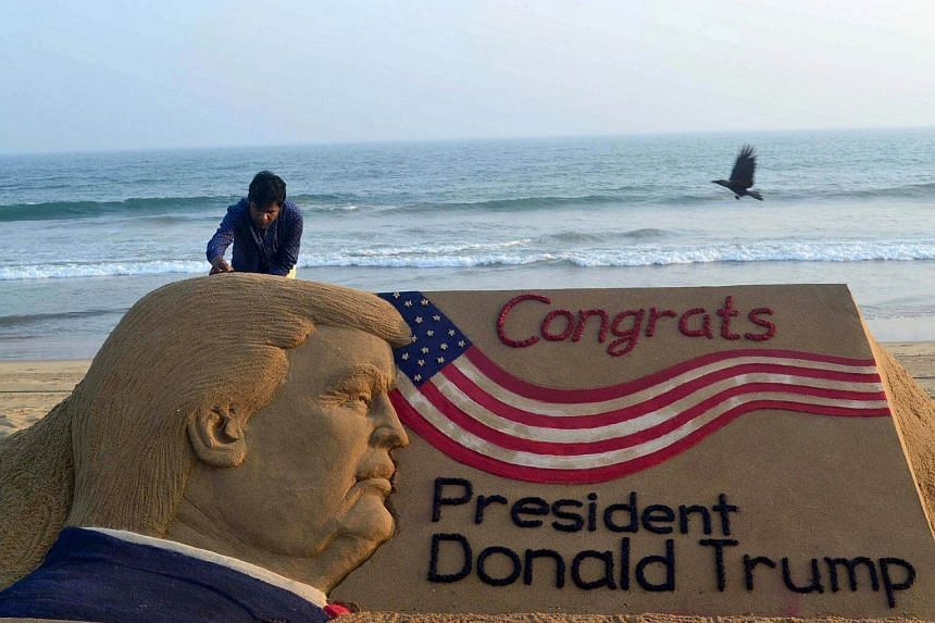 Indian sand artist Sudarsan Pattnaik gives the final touches to his sand sculpture of US President Donald Trump at Puri beach, on Jan 19, 2017.