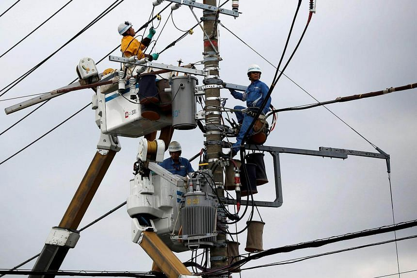 Men work around an electric utility pole along the street in Urayasu, east of Tokyo.