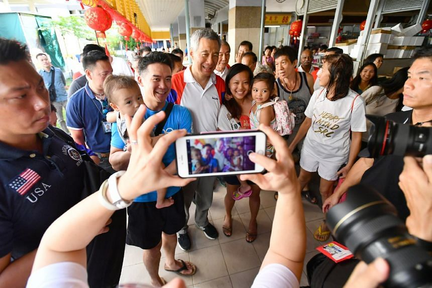 Prime Minister Lee Hsien Loong taking photographs with residents during his walkabout at 341 Ang Mo Kio Ave 1 Market and Food Centre, on Jan 21, 2017.