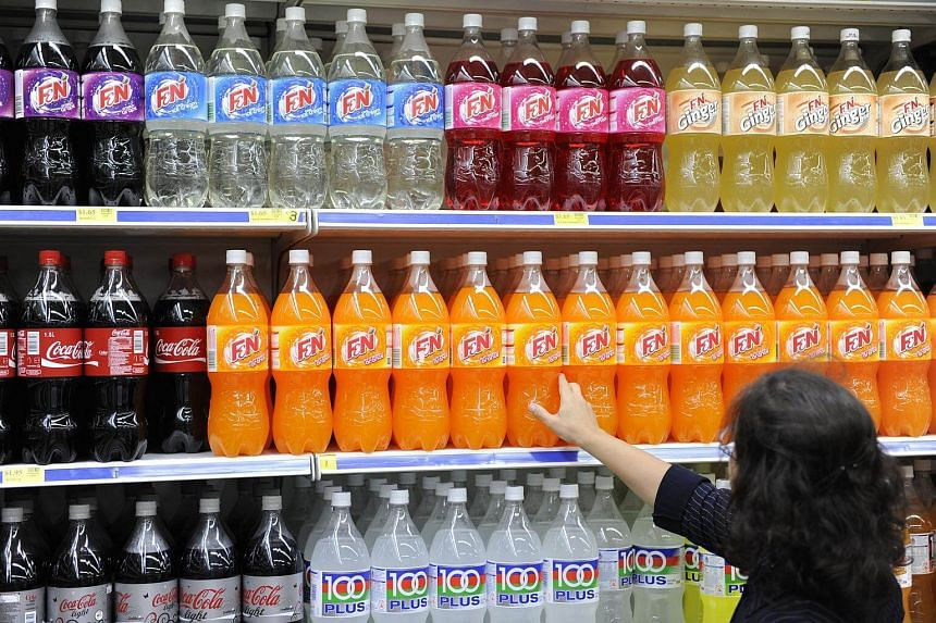 A customer looking at bottles of F&N's soft drinks at a supermarket in Singapore.