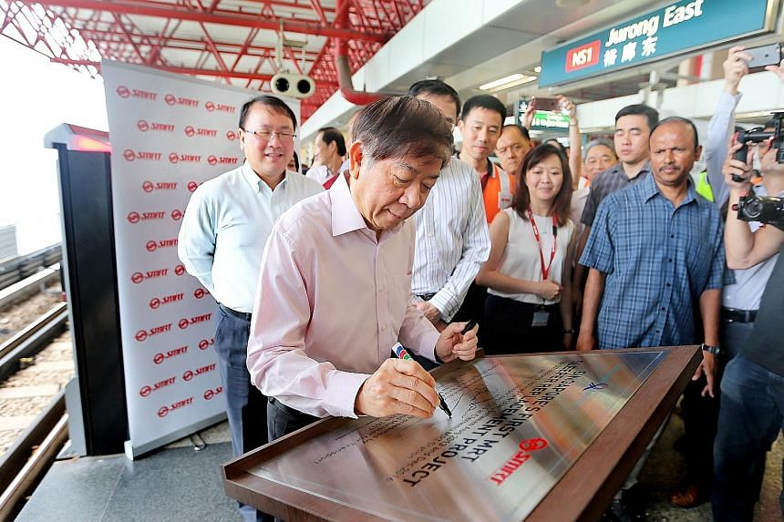 Above, left: Mr Khaw signing a plaque at a ceremony to mark the completion of the sleeper replacement project yesterday. With him are (from far left) LTA's Mr Chua and SMRT's president and group CEO Desmond Kuek (partially hidden). Above, right: The
