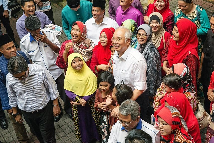 Malaysian Prime Minister Najib Razak posing for photographs with a group of supporters at a Barisan Nasional event in the Titiwangsa area in Kuala Lumpur, Malaysia, yesterday.