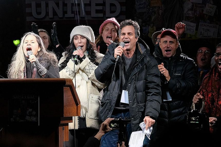 Celebrities (front row, from left) Natalie Merchant, Cher and Mark Ruffalo at the We Stand United NYC Rally outside Trump International Hotel on Thursday night in New York City.