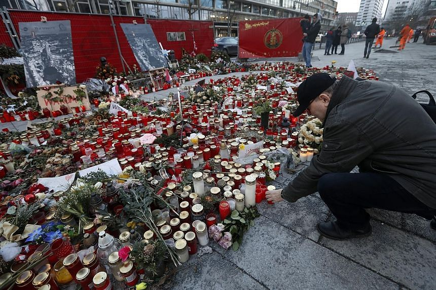 A man paying his respects on Thursday at a memorial site for victims one month after the Berlin Christmas attack carried out by a man who had been under investigation for various reasons. German Interior Minister Thomas de Maiziere said on Wednesday