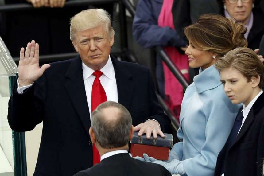 Donald Trump takes the oath of office with his wife Melania and son Barron at his side, during his inauguration at the US Capitol in Washington on Jan 20, 2017.