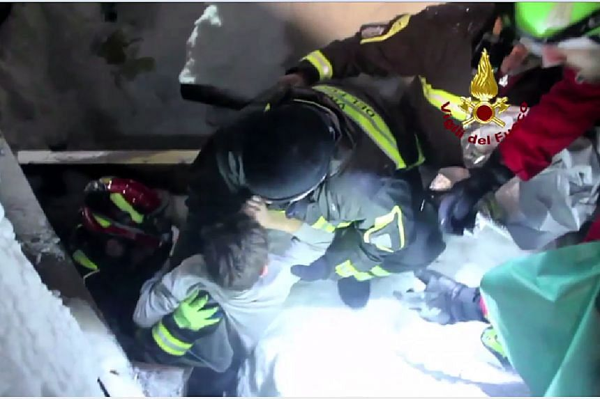 A handout picture released on Jan 20, 2017 by the Vigili del Fuoco shows a child (centre) being rescued from the Hotel Rigopiano, which was engulfed by a powerful avalanche a day before.