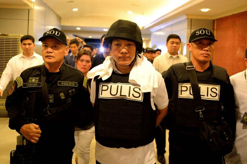 Ricky Sta. Isabel (centre), one of the suspects in the kidnapping and murder of South Korean Jee Ick Joo, is escorted by fellow policemen as they leave the National Bureau of Investigation building in Manila on Jan 20, 2016.