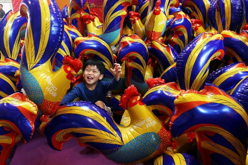 Evan Choo, three, has some fun among the rooster balloons.