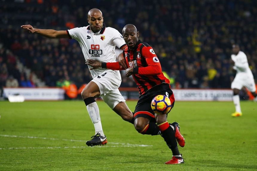Bournemouth's Benik Afobe in action with Watford's Younes Kaboul.