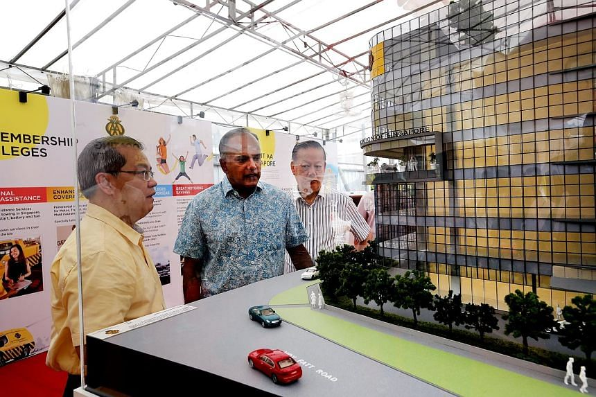 Minister K. Shanmugam viewing a model of the new AA Singapore building with chief executive Lee Wai Mun (left) and president Bernard Tay. He said partners like AA Singapore can help improve road traffic safety.