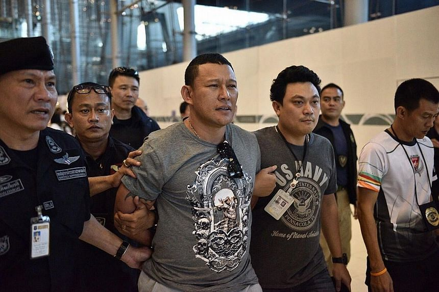 Suspected drug lord from Laos, Xayasana Keopimpha, being escorted by the police after his dramatic arrest in front of dozens of travellers at Suvarnabhumi Airport in Bangkok on Thursday.