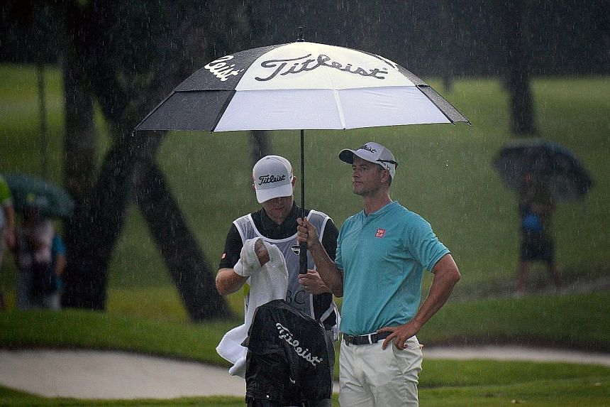 Adam Scott (right) of Australia shelters from the rain as he prepares to line up a shot during the third round of the rain-hit SMBC Singapore Open held at Sentosa Golf Club's Serapong course yesterday.